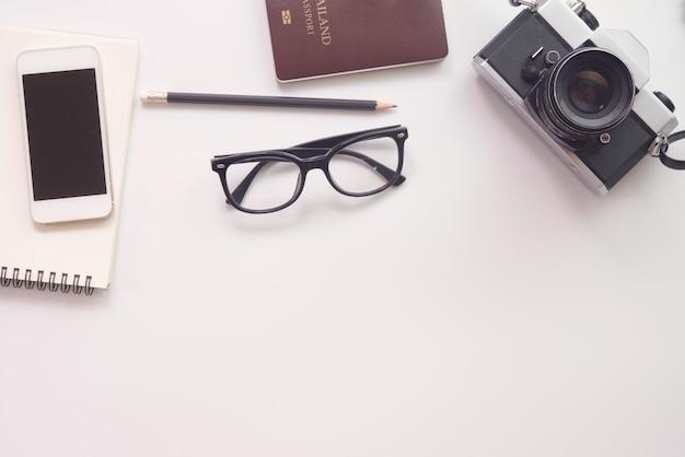 Projeto liso da configuração da mesa do trabalho com caderno, vidros, câmera, smartphone e passaporte no fundo branco.