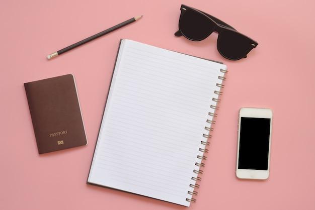 Projeto liso da mesa do espaço de trabalho com vidros e telefone celular vazios do lápis do caderno no fundo da cor pastel do vintage.