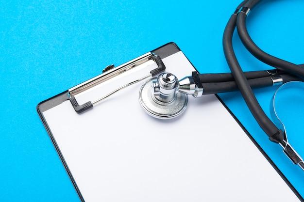 Projeto liso leigo do estetoscópio e almofada de transferência em branco com para conceito médico.