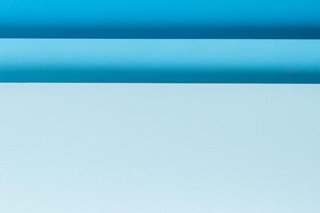 Projeto material de papel dobrado azul colorido horizontalmente. vista superior, configuração plana.