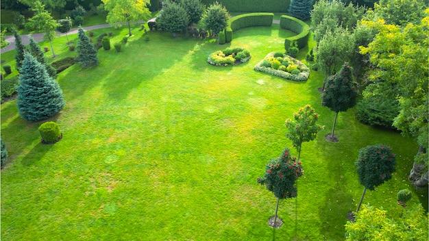 Projeto paisagístico de um parque público. ponte de madeira sobre um rio seco. várias plantas ornamentais crescem em jardins ornamentais. gramado verde perto dos caminhos pavimentados. ótimo lugar para relaxar.