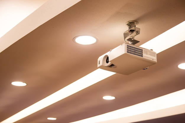 Projetor digital suspenso montado no teto da sala de reuniões.