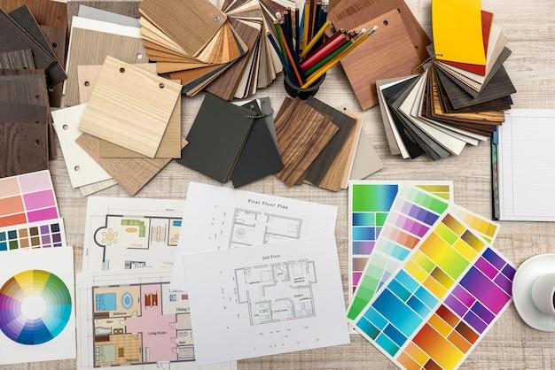 Projetos arquitetônicos com papel e amostrador de cores de madeira na mesa criativa.
