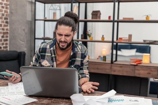 Projetos difíceis. jovem infeliz olhando para a tela do laptop enquanto tem problemas com seu trabalho