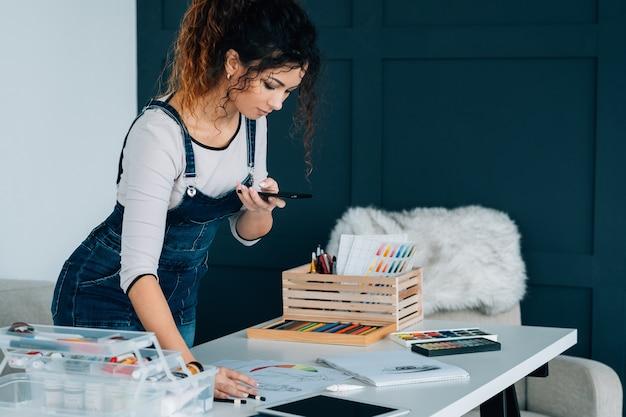 Promoção de mídia social. artista feminina usando a câmera do smartphone para tirar uma foto de seu novo quadro
