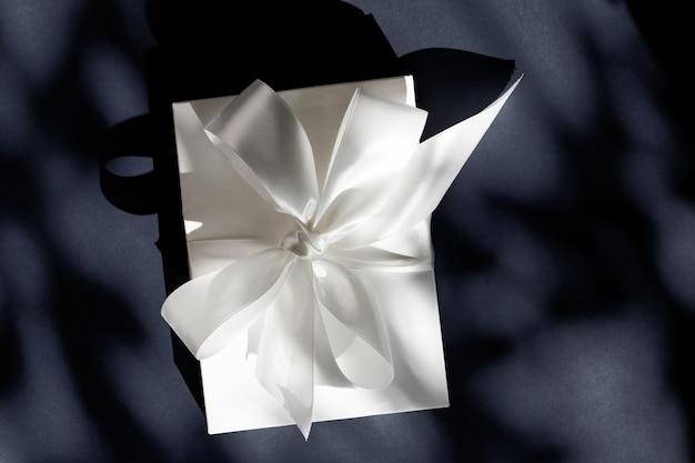Promoção de venda de loja de comemoração de aniversário e conceito surpresa de luxo caixa de presente branca de luxo com fita de seda e arco em fundo preto casamento de luxo ou presente de aniversário