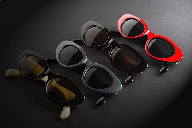 Promoção óptica, poster com óculos de sol em cores diferentes em fundo cinza escuro