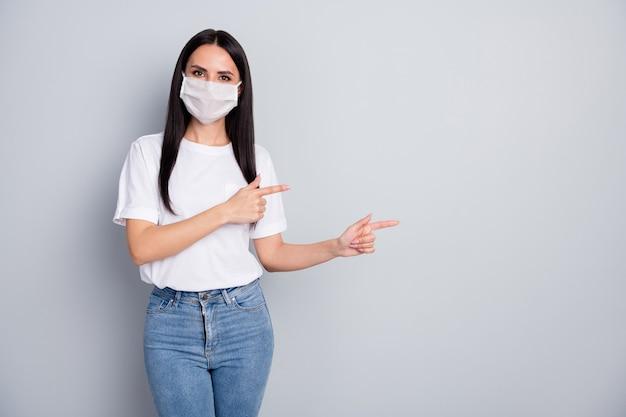 Promotor de garota confiante em máscara médica apontar dedo indicador copyspace demonstrar informações sobre coronavírus apresentar proteção de segurança vestir camiseta branca jeans isolado cor cinza