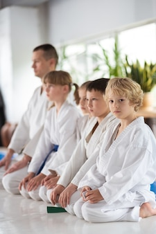 Pronto para a competição. crianças em quimono branco se sentindo prontas para uma importante competição de aikido