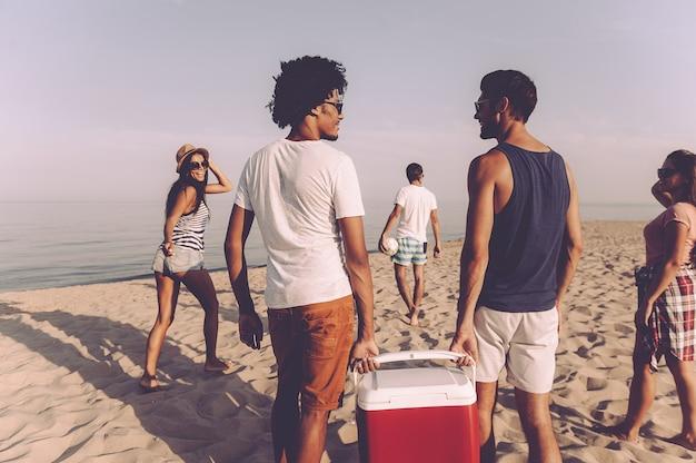 Pronto para a festa na praia. grupo de jovens alegres caminhando pela praia até o mar enquanto dois homens carregando refrigerador de plástico