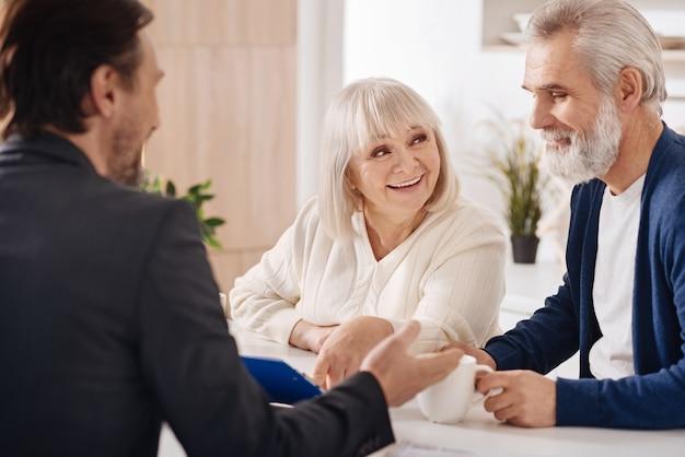 Pronto para assinar. casal idoso alegre e animado sentado em casa conversando com o conselheiro enquanto expressa positividade e discute o contrato