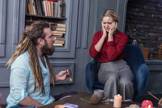 Pronto para chorar. mulher triste e infeliz sentada na poltrona enquanto ouve a previsão negativa