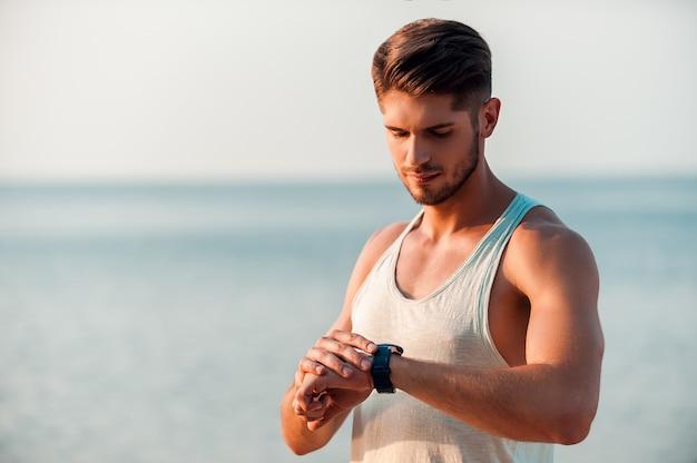 Pronto para combinar com seu tempo. homem jovem e musculoso confiante, verificando as horas em seus relógios enquanto fica ao ar livre