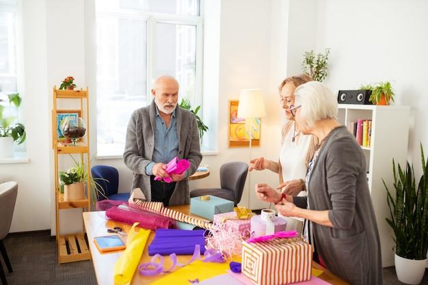 Pronto para comemorar. idosos simpáticos em pé ao redor da mesa enquanto preparam presentes para as festas