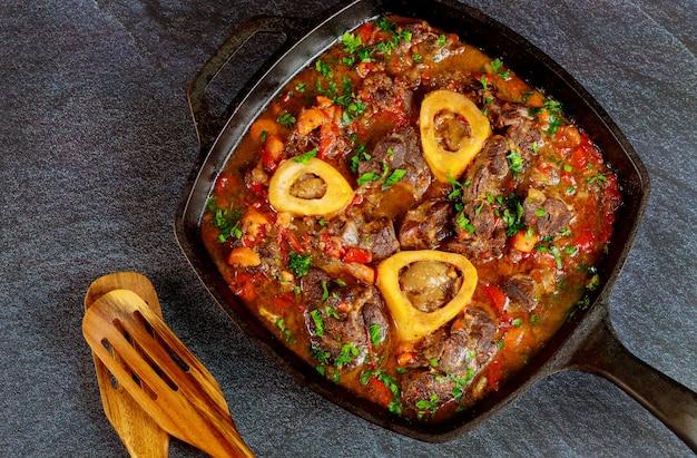 Pronto para comer prato ossobuco servido em ferro fundido.