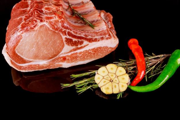 Pronto para cozinhar costelas de porco de carne fresca em fundo preto escuro