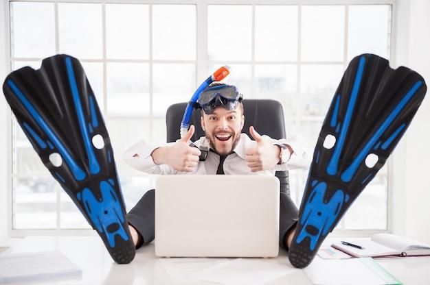 Pronto para férias. trabalhador de escritório jovem e bonito em snorkel e nadadeiras gesticulando e sorrindo enquanto está sentado em seu local de trabalho