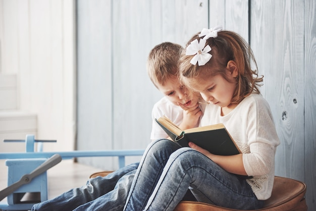 Pronto para grandes viagens. menina feliz e menino lendo livro interessante, carregando uma maleta grande. conceito de liberdade e imaginação