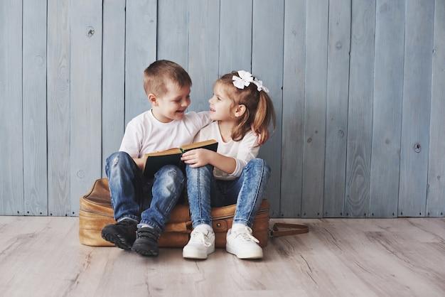 Pronto para grandes viagens. menina feliz e menino lendo livro interessante carregando uma maleta grande e sorrindo. viagem, liberdade e imaginação