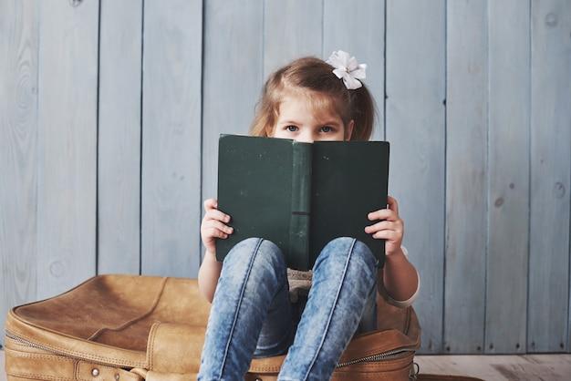 Pronto para grandes viagens. menina feliz lendo livro interessante, carregando uma maleta grande. conceito de liberdade e imaginação