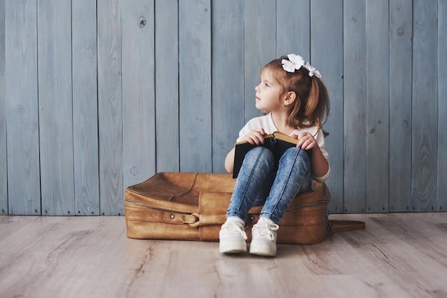 Pronto para grandes viagens. menina feliz lendo livro interessante, carregando uma maleta grande e sorrindo. viagem, liberdade e imaginação