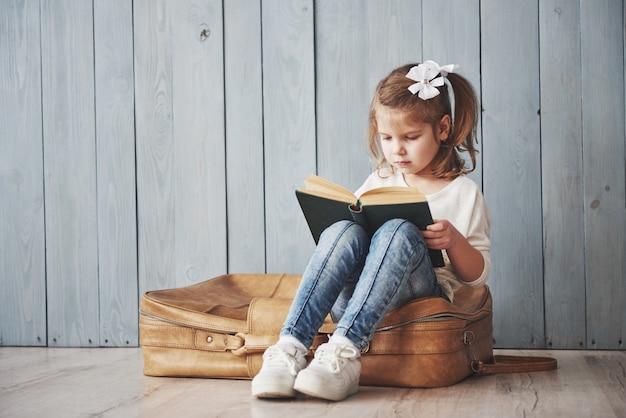 Pronto para grandes viagens. menina feliz lendo livro intereting carregando uma maleta grande e sorrindo. viagem, liberdade e imaginação
