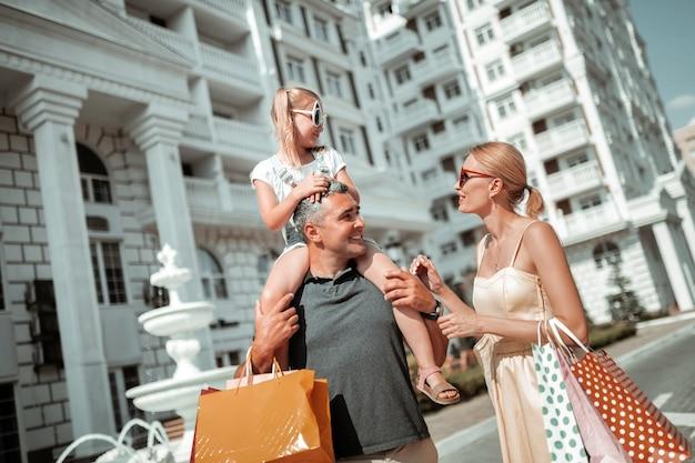 Pronto para ir. uma menina sentada nos ombros de seu pai e conversando com sua mãe, indo para casa depois das compras.