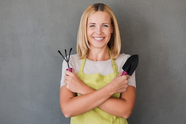 Pronto para jardinagem. mulher madura feliz com avental verde segurando equipamento de jardinagem e sorrindo