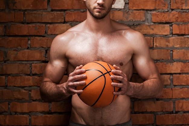 Pronto para jogar bola. imagem recortada de jovem homem musculoso segurando uma bola de basquete