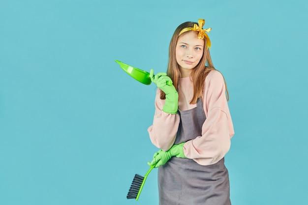Pronto para limpeza de primavera. retrato de menina alegre com suprimentos domésticos nas mãos sobre a parede azul. jovem mulher segura pá e escova.