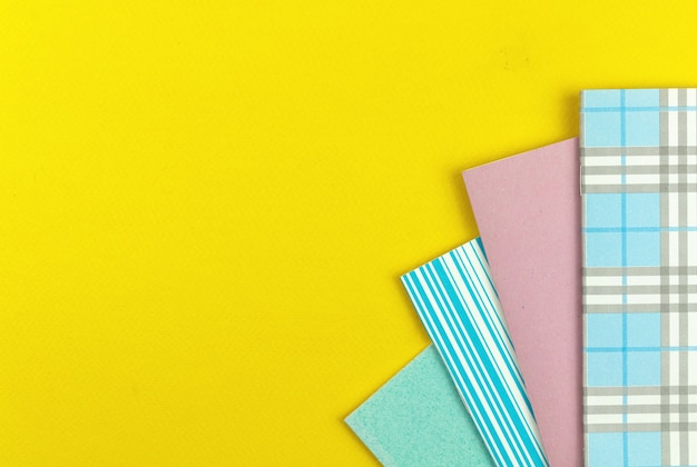 Pronto para o fundo de composição da escola com cadernos coloridos da escola na mesa amarela, foto da vista superior