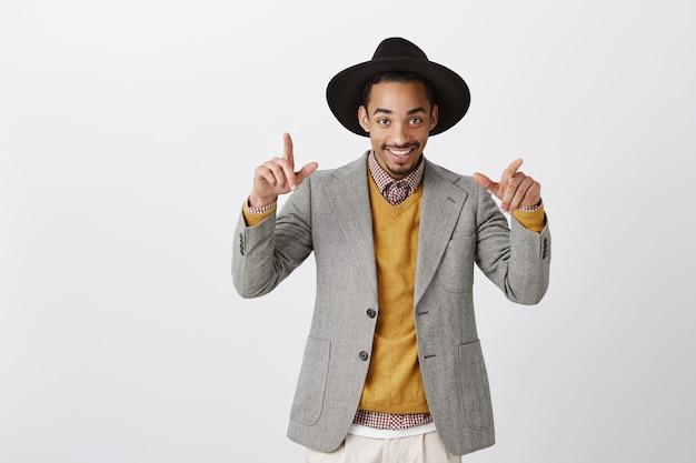 Pronto para relaxar na festa atrevida. retrato de um afro-americano rico e bonito com roupa estilosa e chapéu redondo, fazendo gestos legais enquanto dança ou sai com amigos sobre uma parede cinza