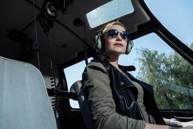 Pronto para trabalhar. alegre piloto de helicóptero esperando por um passageiro enquanto se prepara para iniciar um vôo