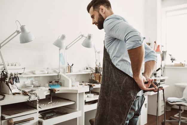 Pronto para trabalhar. retrato de jovem joalheiro ajustando o avental e pronto para começar a trabalhar em sua oficina