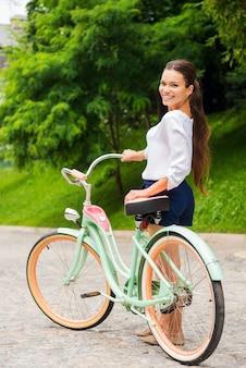 Pronto para um passeio. mulher jovem e atraente sorridente andando com sua bicicleta vintage e olhando para a câmera