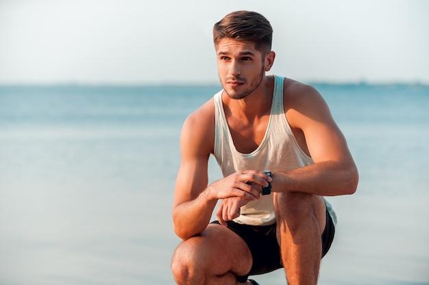 Pronto para vencer seu tempo. jovem pensativo e musculoso, verificando as horas em seus relógios enquanto está sentado ao ar livre