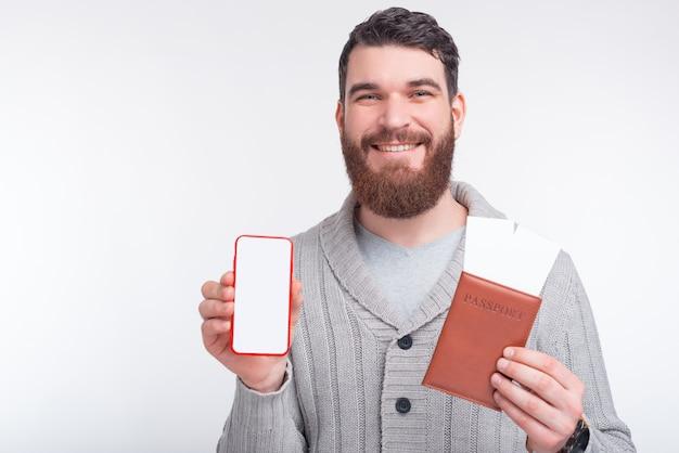 Pronto para voar. compre bilhetes no seu telefone. homem detém passaporte com dois bilhetes enquanto mostra seu telefone de tela em branco para a câmera.