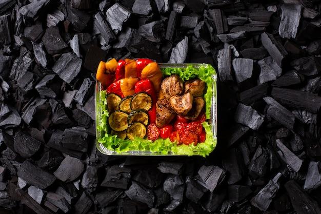 Pronto shish kebab. porção de carne grelhada e vegetais em um recipiente descartável no carvão
