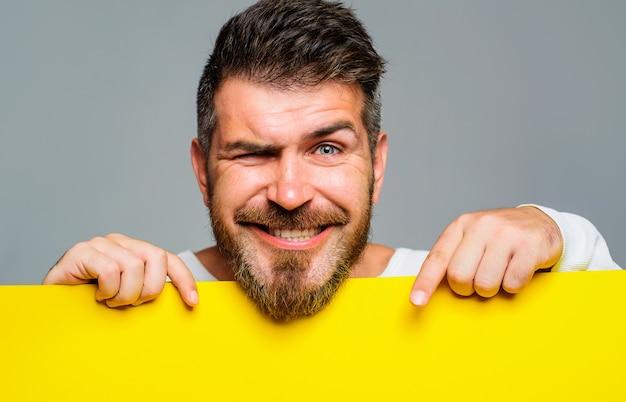Propaganda. homem barbudo sorridente com banner de publicidade. homem feliz com um cartaz vazio ou uma placa em branco com espaço de cópia.