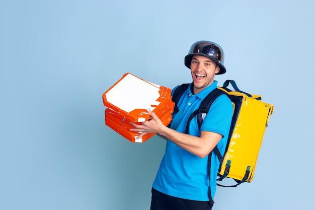Propondo pizza. emoções de entregador caucasiano isolado na parede azul