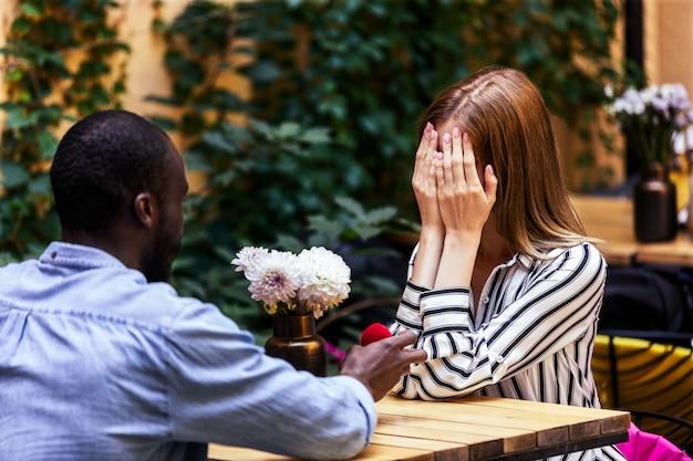 Proposta do garoto africano para uma garota caucasiana no terraço de um aconchegante restaurante ao ar livre