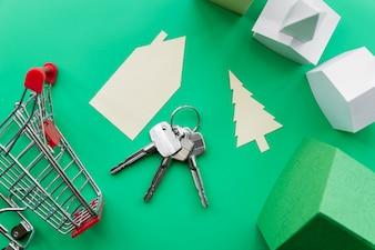 Propriedade imobiliária feita com casas com chaves e carrinho de compras em fundo verde