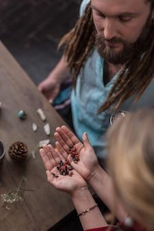 Propriedades mágicas. vista superior de mãos femininas com sementes especiais e propriedades mágicas