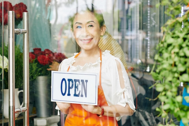 Proprietária de floricultura sênior sorridente com avental laranja virando sinal aberto na porta de vidro