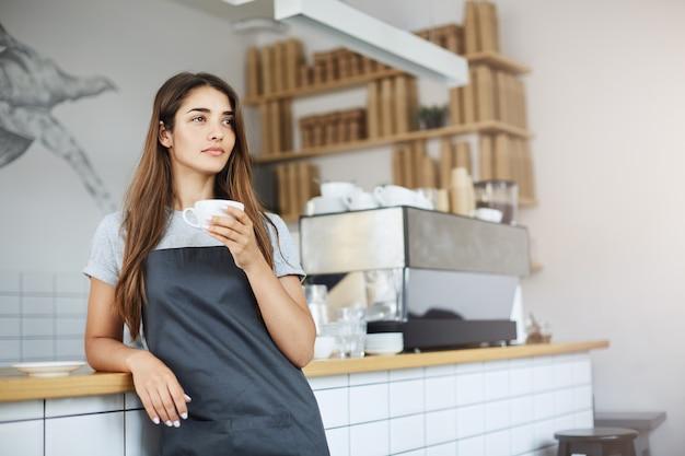 Proprietária de loja em pausa de seu trabalho como barista sonhando com um negócio maior
