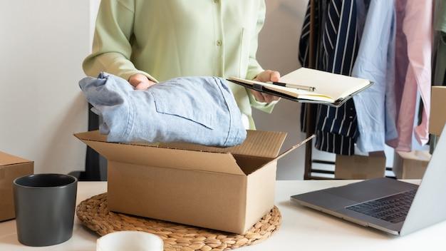 Proprietária de uma empresa asiática trabalhando em casa com a caixa de embalagem de sua loja online se prepara para entregar produtos aos clientes, conceito de estilo de vida da geração alfa