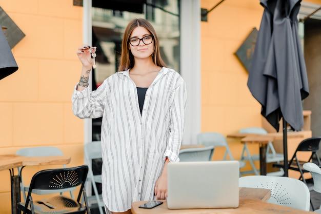 Proprietário da empresa feminina com chaves de café e laptop