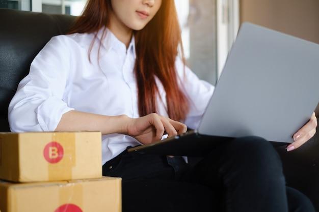 Proprietário da empresa trabalhando em embalagens de escritório em casa. empreendedor de pequenas e médias empresas de compras online ou conceito de trabalho freelance.