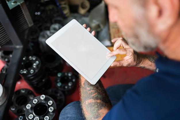 Proprietário da loja de reparação de automóveis que verifica o conceito da tabuleta