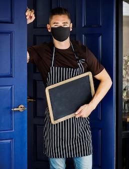Proprietário da loja na máscara do lado de fora do café em novo normal com uma placa